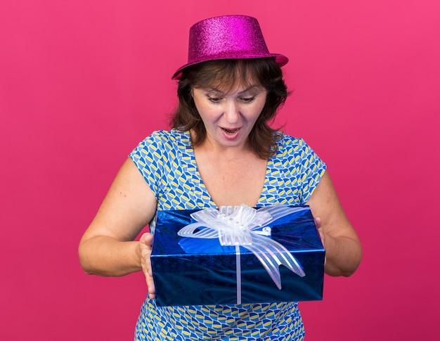 Vrouw van middelbare leeftijd met feestmuts die een cadeautje vasthoudt en er verbaasd naar kijkt