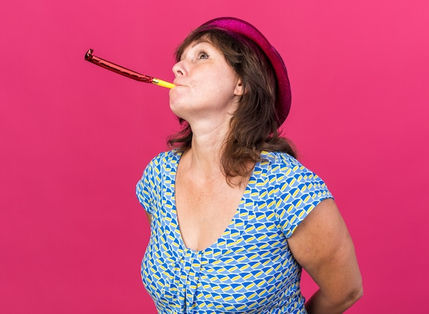Vrouw van middelbare leeftijd met feestmuts die op een fluitje blaast en verbaasd opkijkt om een verjaardagsfeestje te vieren dat over een roze muur staat