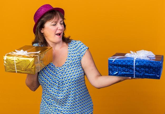 Vrouw van middelbare leeftijd met feestmuts die verjaardagscadeautjes vasthoudt en ze vrolijk en vrolijk glimlachend breed bekijkt