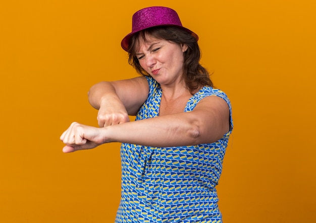 Vrouw van middelbare leeftijd met feestmuts die verward en ontevreden met gebalde vuisten kijkt en verjaardagsfeestje viert dat over oranje muur staat