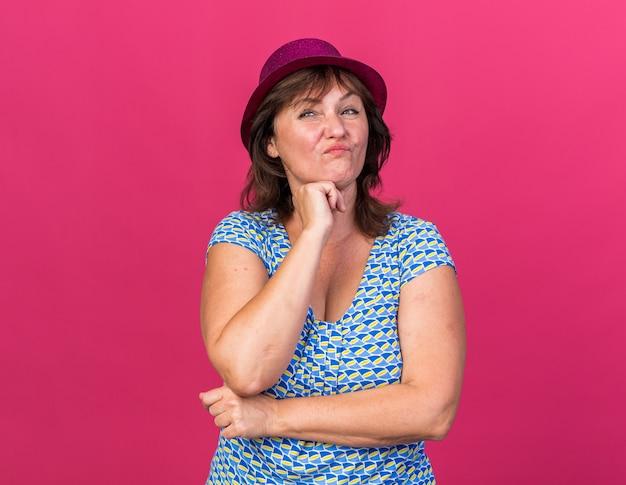 Vrouw van middelbare leeftijd met feestmuts opzij kijkend met sceptische uitdrukking