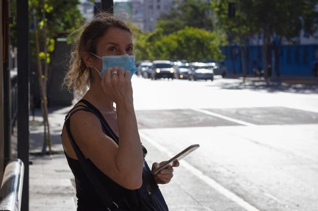 Vrouw van middelbare leeftijd met gezichtsbedekking wachtend op het busstation met mobiele telefoon eenzame dame met masker