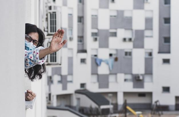 Vrouw van middelbare leeftijd met gezichtsmasker die vanuit haar raam afscheid neemt van een familielid. thuis geïsoleerd. achtergrond van woongebouwen.