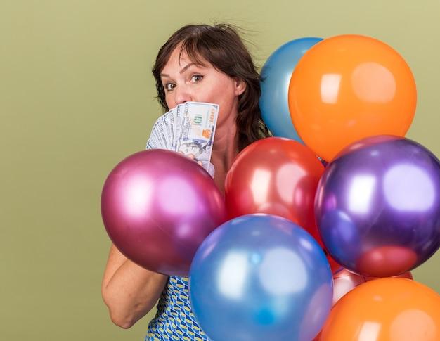 Vrouw van middelbare leeftijd met kleurrijke ballonnen die contant geld vasthouden, blij en verrast om een verjaardagsfeestje te vieren dat over de groene muur staat