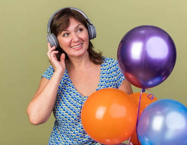 Vrouw van middelbare leeftijd met koptelefoon en bos kleurrijke ballonnen blij en vrolijk genietend van haar favoriete muziek