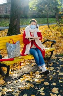 Vrouw van middelbare leeftijd met medisch masker op gele bank