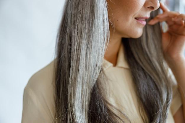 Vrouw van middelbare leeftijd met mooi grijs haar vormt op lichtgrijze achtergrond in studio close-up. volwassen schoonheid levensstijl