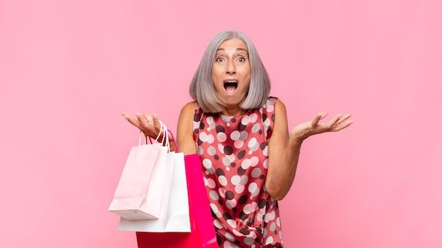 Vrouw van middelbare leeftijd met open mond en verbaasd, geschokt en verbaasd