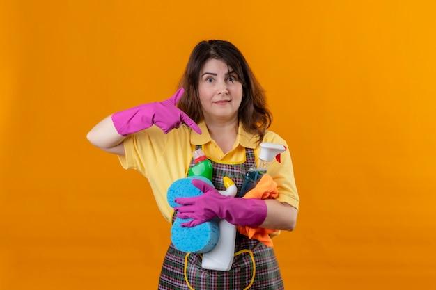 Vrouw van middelbare leeftijd met schort en rubberen handschoenen met schoonmaakbenodigdheden die met de vinger naar hen wijzen glimlachend vriendelijk positief en gelukkig staande over oranje muur 2