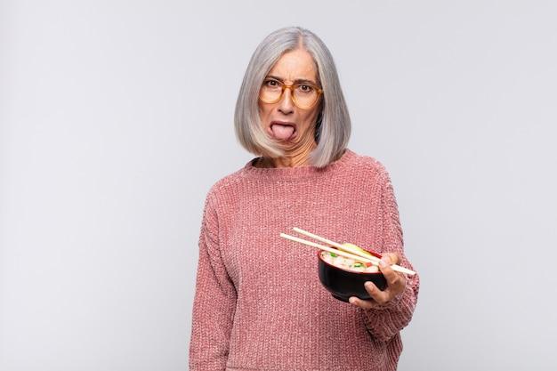 Vrouw van middelbare leeftijd met vrolijke, zorgeloze, opstandige houding, grapje en tong uitsteekt, plezier aziatisch eten concept