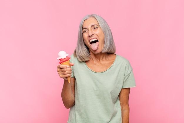 Vrouw van middelbare leeftijd met vrolijke, zorgeloze, rebelse houding, grappen maken en tong uitsteken, plezier hebben met een ijsje