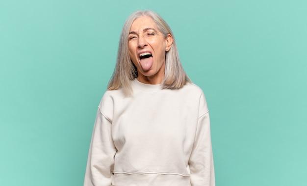 Vrouw van middelbare leeftijd met vrolijke, zorgeloze, rebelse houding, grappen maken en tong uitsteken