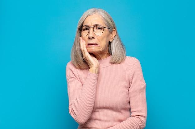 Vrouw van middelbare leeftijd met wang en pijnlijke kiespijn, zich ziek, ellendig en ongelukkig voelen, op zoek naar een tandarts