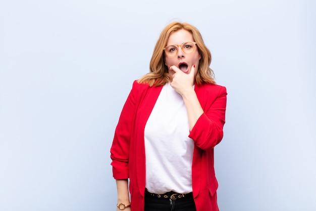 Vrouw van middelbare leeftijd met wijd open mond en ogen en hand op kin, zich onaangenaam geschokt, zegt wat of wauw