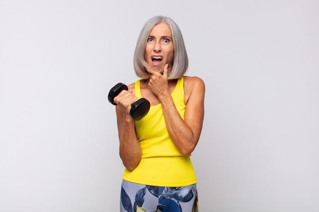 Vrouw van middelbare leeftijd met wijd open mond en ogen en hand op kin