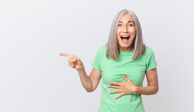 Vrouw van middelbare leeftijd met wit haar die hardop lacht om een hilarische grap en naar de zijkant wijst