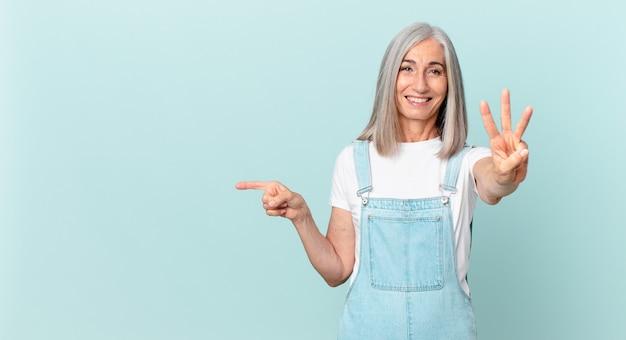 Vrouw van middelbare leeftijd met wit haar die lacht en er vriendelijk uitziet, nummer drie toont en naar de zijkant wijst