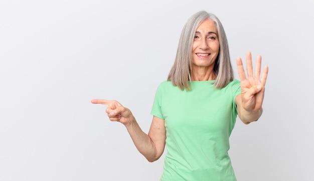 Vrouw van middelbare leeftijd met wit haar die lacht en er vriendelijk uitziet, nummer vier toont en naar de zijkant wijst