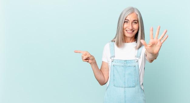 Vrouw van middelbare leeftijd met wit haar die lacht en er vriendelijk uitziet, nummer vijf toont en naar de zijkant wijst