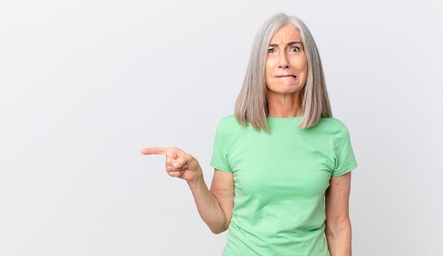 Vrouw van middelbare leeftijd met wit haar die verbaasd en verward kijkt en naar de zijkant wijst