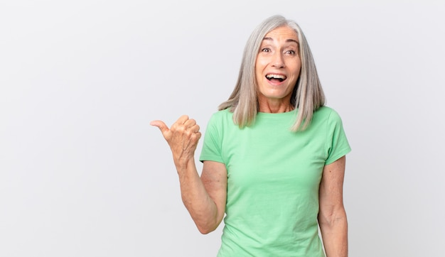 Vrouw van middelbare leeftijd met wit haar die verbaasd kijkt in ongeloof en naar de zijkant wijst
