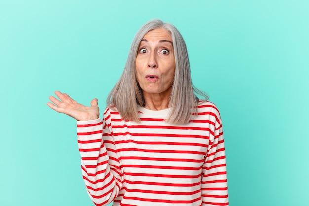 Vrouw van middelbare leeftijd met wit haar die verrast en geschokt kijkt, met open mond terwijl ze een voorwerp vasthoudt