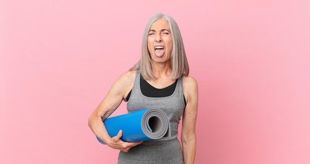 Vrouw van middelbare leeftijd met wit haar die walgt en geïrriteerd voelt en tong uitsteekt en een yogamat vasthoudt