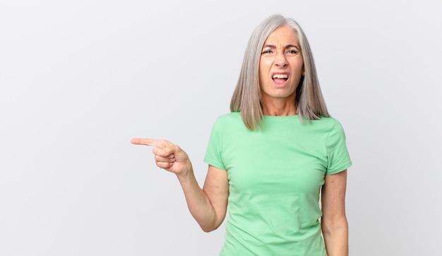 Vrouw van middelbare leeftijd met wit haar die zich verbaasd en verward voelt en naar de zijkant wijst