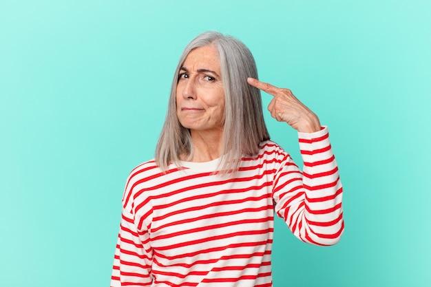 Vrouw van middelbare leeftijd met wit haar die zich verward en verbaasd voelt en laat zien dat je gek bent