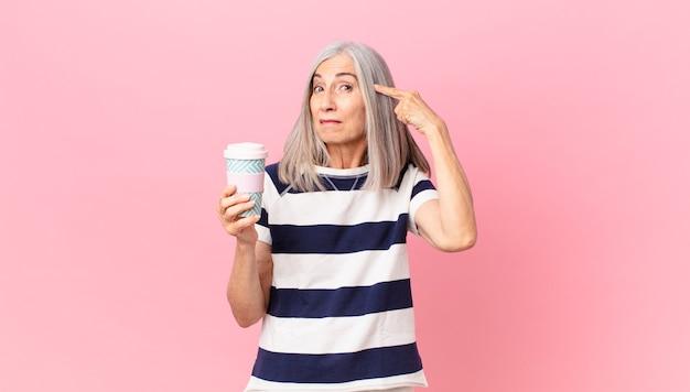 Vrouw van middelbare leeftijd met wit haar die zich verward en verbaasd voelt, laat zien dat je gek bent en een afhaalkoffiecontainer vasthoudt
