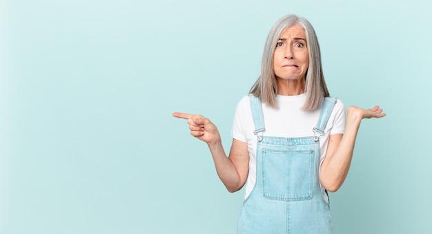 Vrouw van middelbare leeftijd met wit haar die zich verward en verward voelt en twijfelt en naar de zijkant wijst