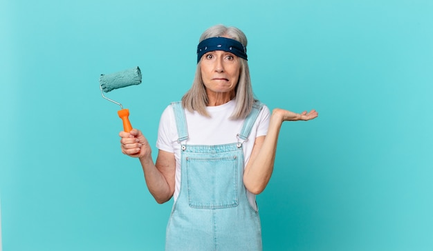 Vrouw van middelbare leeftijd met wit haar die zich verward en verward voelt en twijfelt met een roller die een muur schildert