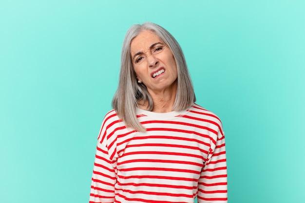 Vrouw van middelbare leeftijd met wit haar die zich verward en verward voelt