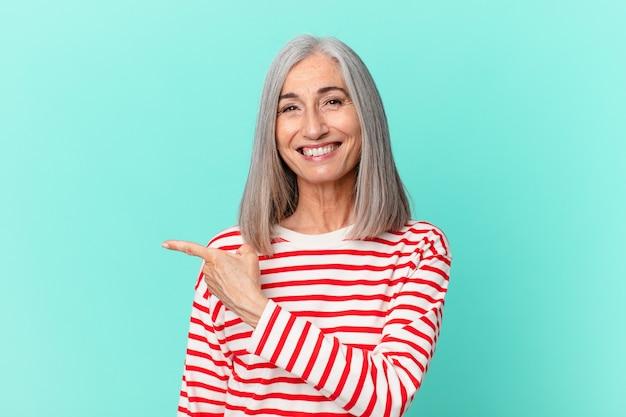 Vrouw van middelbare leeftijd met wit haar lacht vrolijk, voelt zich gelukkig en wijst naar de zijkant