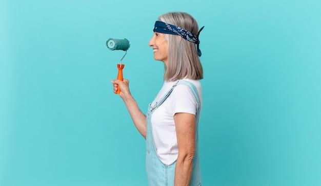 Vrouw van middelbare leeftijd met wit haar op profielaanzicht denkend, fantaserend of dagdromen met een roller die een muur schildert