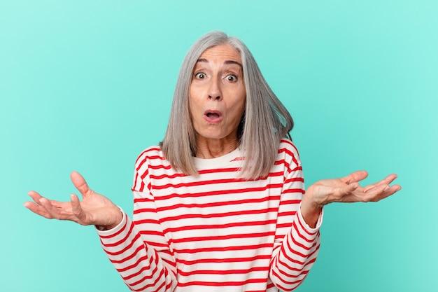 Vrouw van middelbare leeftijd met wit haar verbaasd, geschokt en verbaasd met een ongelooflijke verrassing