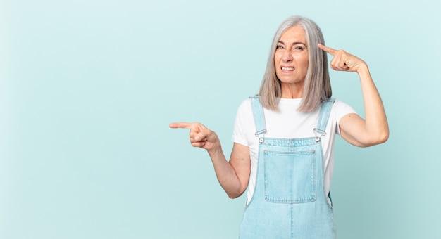 Vrouw van middelbare leeftijd met wit haar voelt zich verward en verbaasd, laat zien dat je gek bent en wijst naar de zijkant