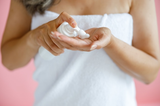 Vrouw van middelbare leeftijd omwikkeld met handdoek knijpt schuim op palm uit fles op roze achtergrond in studio close-up. volwassen schoonheid levensstijl