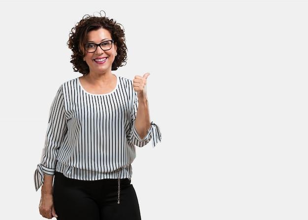 Vrouw van middelbare leeftijd opgewekt en opgewonden, glimlachend en haar duim omhoog verhogen