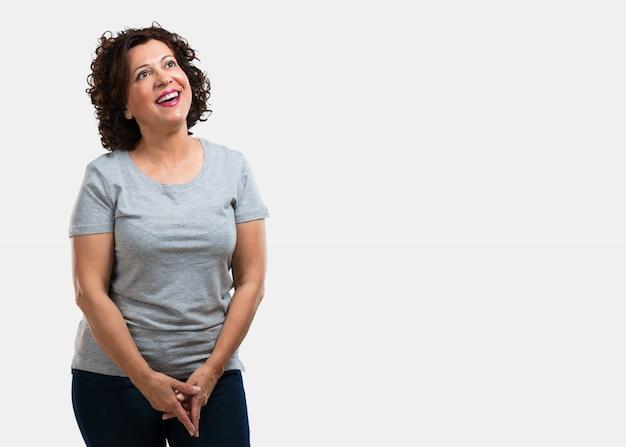 Vrouw van middelbare leeftijd opzoeken, denken aan iets leuks en het hebben van een idee, concept van de verbeelding