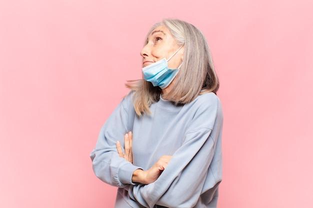 Vrouw van middelbare leeftijd schouderophalend gevoel verward en onzeker twijfelen met gekruiste armen en verbaasde blik
