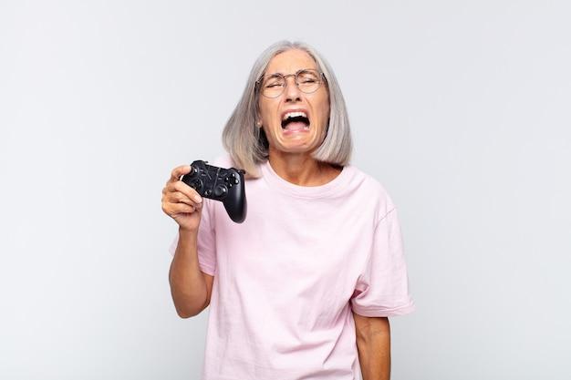 Vrouw van middelbare leeftijd schreeuwen agressief, erg boos geïsoleerd kijken