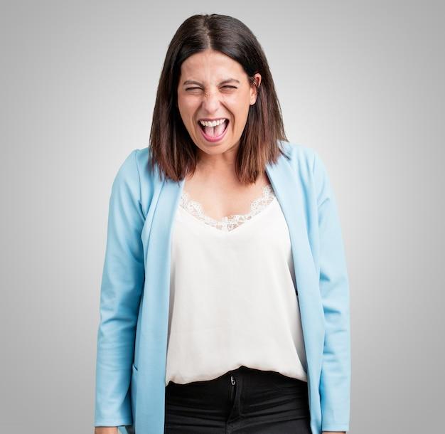 Vrouw van middelbare leeftijd schreeuwen boos, uitdrukking van waanzin en mentale instabiliteit, open mond en half geopende ogen, waanzin concept