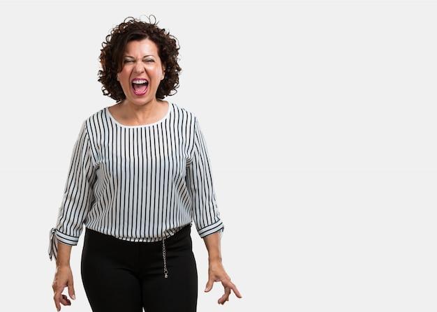 Vrouw van middelbare leeftijd schreeuwen boos, uitdrukking van waanzin en mentale instabiliteit