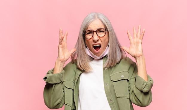 Vrouw van middelbare leeftijd schreeuwen met handen in de lucht, woedend, gefrustreerd, gestrest en boos