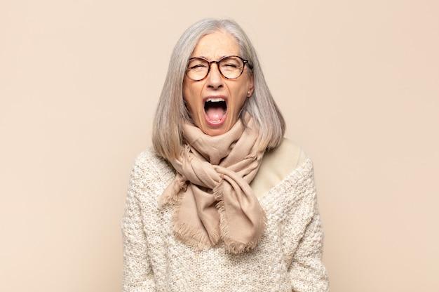 Vrouw van middelbare leeftijd schreeuwt agressief, kijkt erg boos, gefrustreerd, verontwaardigd of geïrriteerd