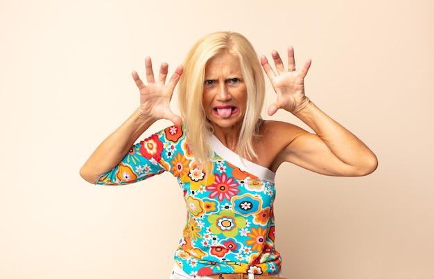 Vrouw van middelbare leeftijd schreeuwt in paniek of woede, geschokt, doodsbang of woedend, met de handen naast het hoofd