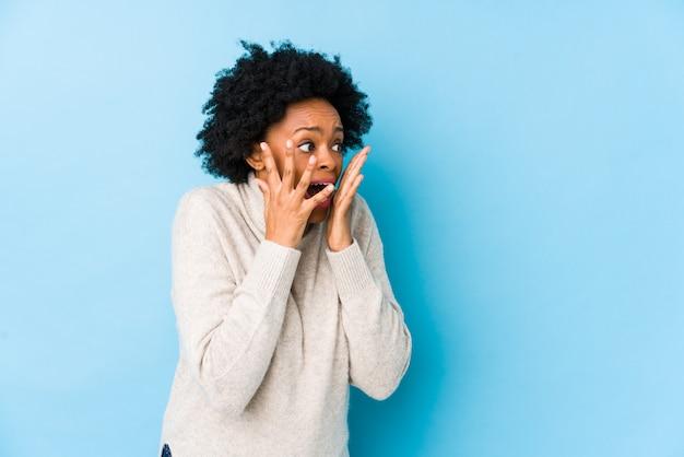 Vrouw van middelbare leeftijd schreeuwt luid, houdt ogen open en handen gespannen