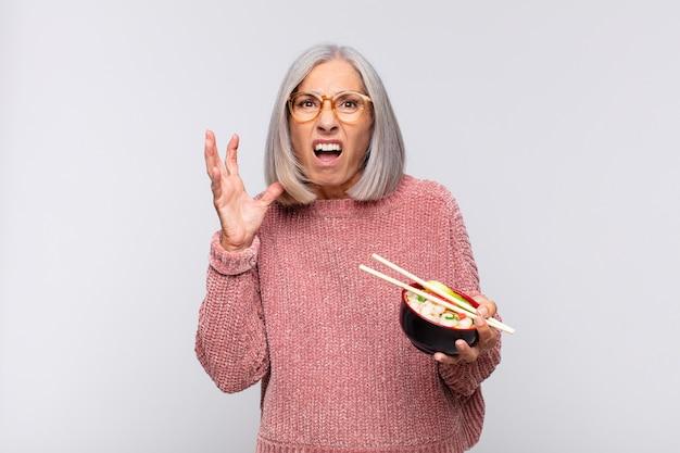 Vrouw van middelbare leeftijd schreeuwt met de handen in de lucht, voelt zich woedend, gefrustreerd, gestrest en overstuur aziatisch voedselconcept