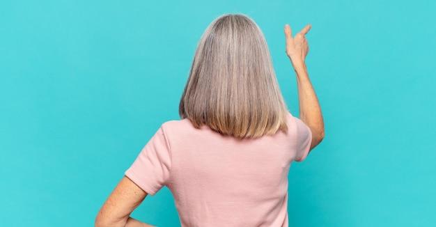Vrouw van middelbare leeftijd staan ?? en wijst naar bezwaar op kopie ruimte, achteraanzicht
